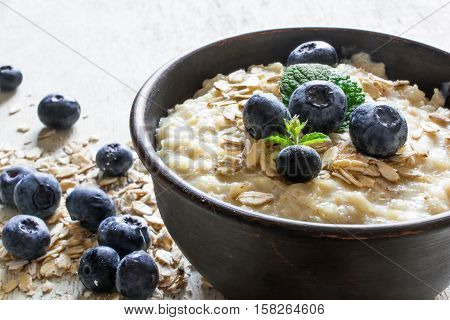 oatmeal porridge with ripe blueberries for healthy breakfast on rustic wooden background. close up