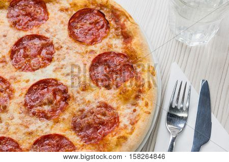 Detail of delicious salami pizza on the table