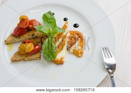 Delicious toast sandwiches with fried cheese tomatoes olive oil and basil