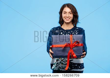 Young beautiful brunette girl in cosy knited sweater smiling holding gift box over blue background. Copy space.