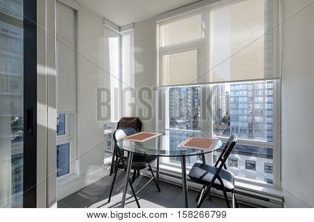 Bright apartment solarium dining room with a view of downtown. Interior design.