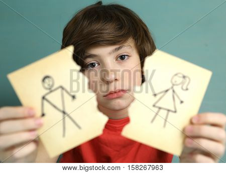 preteen handsome boy hold mom and dad drawing torn apart with sad expression close up photo