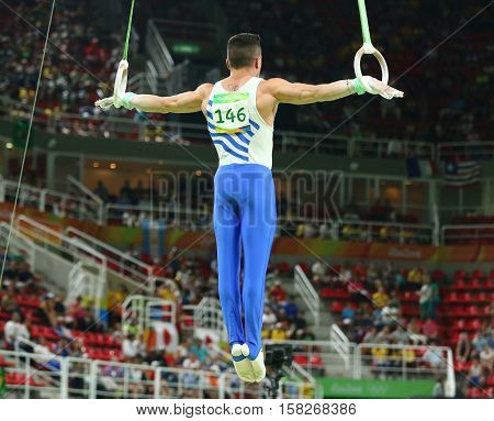 RIO DE JANEIRO, BRAZIL - AUGUST 15, 2016: Olympic champion Eleftherios Petrounias of Greece competes at the Men's Rings Final on artistic gymnastics competition at Rio 2016 Olympic Games