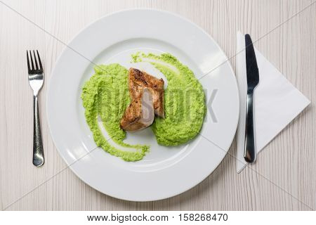 Detail of grilled chicken steak with mashed green peas up on a plate