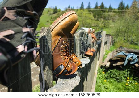 Wet and muddy shoes after a hike to the top of the mountain to dry on the fence. Many pairs of sports shoes