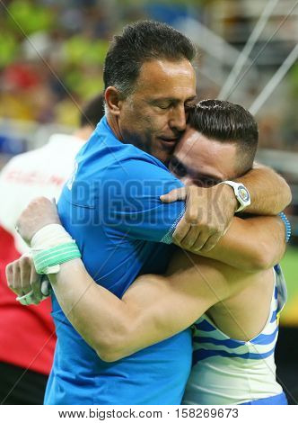 RIO DE JANEIRO, BRAZIL - AUGUST 15, 2016: Olympic champion Eleftherios Petrounias of Greece (R) with his coach after Men's Rings Final on artistic gymnastics competition at Rio 2016 Olympic Games