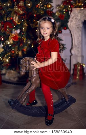little girl three years old in a red dress smiling and riding on a wooden horse toy