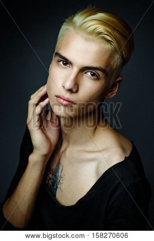 handsome young blond man. Male beauty concept. Portrait of fashionable young man with stylish haircut, on gray background. Perfect hair & skin. Hipster style.