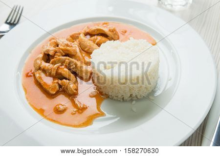 Chicken meat with sauce and rice in a restaurant