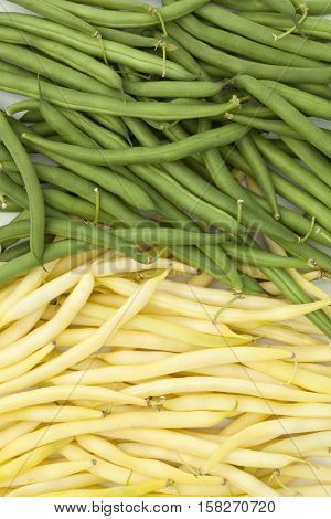 two heaps green and yellow beans lies on table