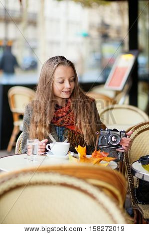 Beautiful Young Woman In A Cafe Holding An Old-fashioned Photo Camera