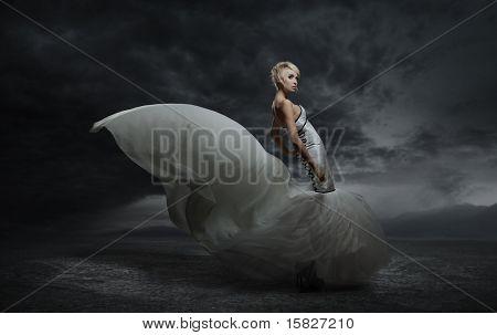 Young Beauty Woman tragen prächtigen Kleid Standing gegenüber dem dunklen Himmel Hintergrund