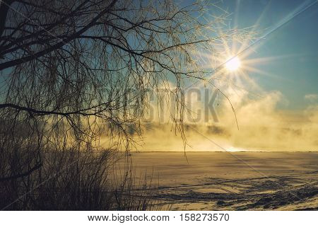 Winter landscape in sunrise - morning winter mist on the winter river covered with winter snow and ice. Winter snow landscape scene in warm tones - beautiful winter snow nature in sunlight