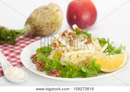 Waldorf salad with red apple, celery and walnuts over white background