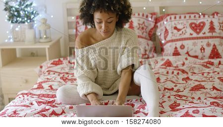 Woman in oversized sweater on bed using laptop