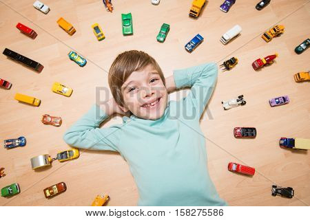 Portrait of happy boy lying on the ground with toy cars around him