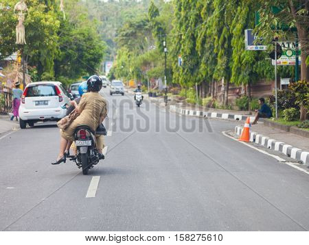 BALI / INDONESIA - NOVEMBER 12 2013: a woman drives on a motorbike in Bali / Indonesia