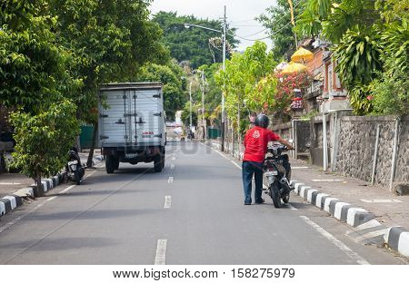 BALI / INDONESIA - NOVEMBER 12 2013: a motorbike driver pushes his motorbike on a road