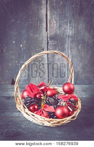 Christmas decorations lay in a wicker basket. Christmas background. Christmas decorations. New Year background. Xmax background. Toned image.