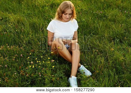 Attractive girl sitting cross-leged with her mobile phone on a grass wearing a white T-shirt and trainers. A gaze into a cell phone
