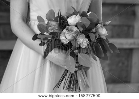 The bride holds a wedding bouquet. The bride's bouquet. Black and white. Close-up.