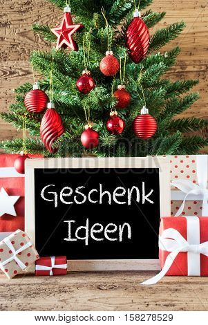 Chalkboard With German Text Geschenk Ideen Means Gift Ideas. Colorful Christmas Card For Seasons Greetings. Christmas Tree With Balls. Gifts Or Presents In The Front Of Wooden Background.