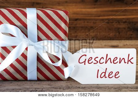 German Text Geschenk Idee Means Gift Idea. Macro Of Christmas Gift Or Present On Wooden Background. Card For Seasons Greetings, Best Wishes Or Congratulations. White Ribbon With Bow.