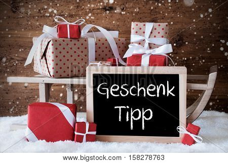 Chalkboard With German Text Geschenk Tipp Means Gift Tip. Sled With Christmas And Winter Decoration And Snowflakes. Gifts And Presents On Snow With Wooden Background.