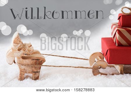 Moose Is Drawing A Sled With Red Gifts Or Presents In Snow. Christmas Card For Seasons Greetings. Silver Background With Bokeh Effect. German Text Willkommen Means Welcome