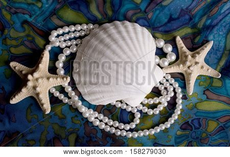 Still-life with cockleshells, starfish and pearls on blue background