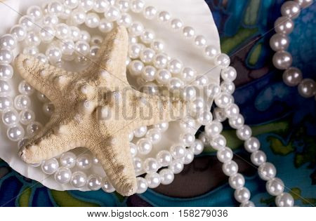 Still-life with cockleshell, starfish and pearls on blue background