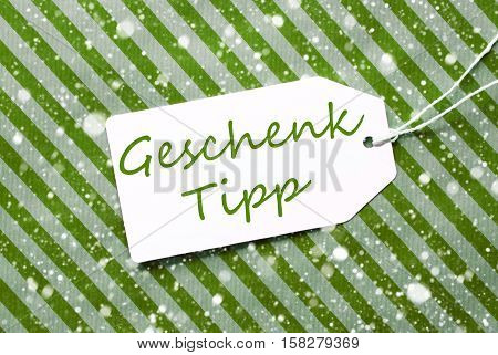 German Text Geschenk Tipp Means Gift Tip. One Label On A Green Striped Wrapping Paper. Textured Background With Snowflakes. Tag With Ribbon.