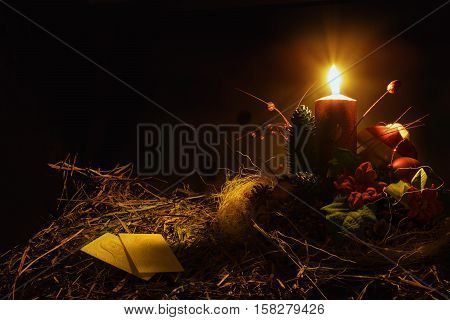 Christmas decoration with wafers and candle. Black background. Warm tone.