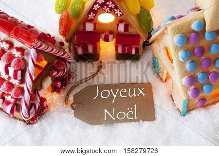 Label With French Text Joyeux Noel Means Merry Christmas. Colorful Gingerbread House On Snow. Christmas Card For Seasons Greetings