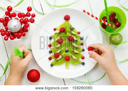 Funny edible Christmas tree for kids breakfast or dessert. Christmas treats for children. Baby eating Christmas food composition top view