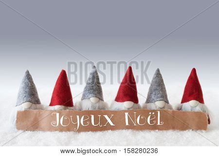 Label With French Text Joyeux Noel Means Merry Christmas. Christmas Greeting Card With Gnomes. Silver Background With Snow.