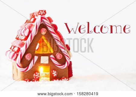 Gingerbread House In Snowy Scenery As Christmas Decoration With White Background. Candlelight For Romantic Atmosphere. English Text Welcome