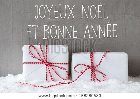 French Text Joyeux Noel Et Bonne Annee Means Merry Christmas And Happy New Year. Two White Christmas Gifts Or Presents On Snow. Cement Wall As Background. Modern And Urban Style.
