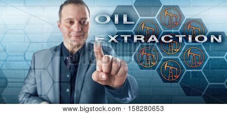 Smiling businessman is activating the phrase OIL EXTRACTION on an interactive control screen. Technology concept and business metaphor for the petroleum industry and onshore crude oil production.