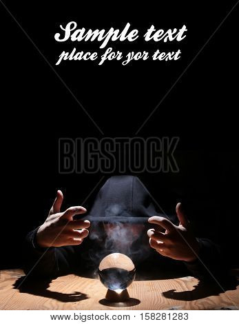 man in a black hood with crystal ball summon evil and empty space for text