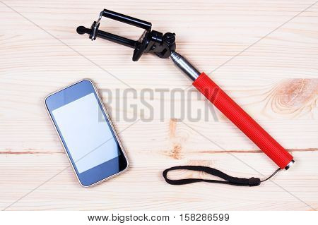 Monopod and phone on wood desk. Gadgetry on board,