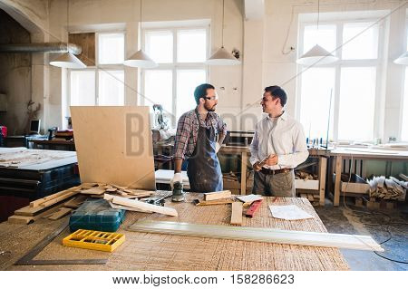 Happy male carpenter showing something to coworker carrying wooden planks in workshop.