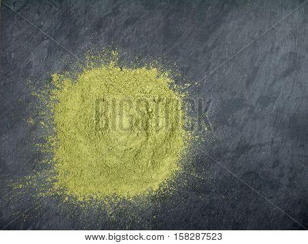 Indigo indigofera tinctoria powder pile on the dark slate