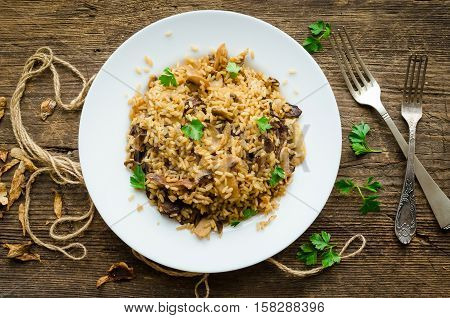 Homemade traditional Italian mushroom risotto on wooden table. Classic Risotto with mushrooms and vegetables served on a white plate. Wild mushrooms risotto with parsley. Top view.