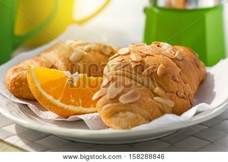 Breakfast With Coffee On Hotel's Balcony, Fresh Croissants And Slice Of Orange Fruit