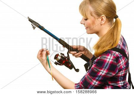 Fishing concept. Attractive woman in dungarees pink check shirt holding and looking at rod. Isolated background