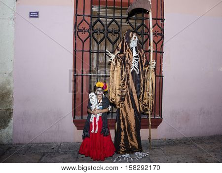 OAXACA, OAXACA, MEXICO - NOVEMBER 1, 2016: Little girl dressed up like Frida Kahlo poses with the Death at day of the dead celebration in Oaxaca, Oaxaca, Mexico