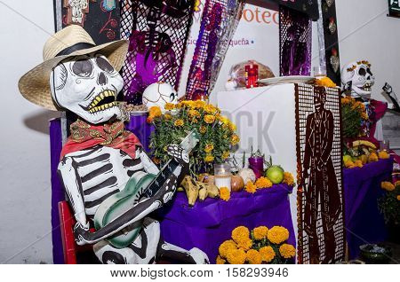 OAXACA, OAXACA, MEXICO - NOVEMBER 1, 2016: Part of a day of the dead offering altar with big skulls made of paper, flowers and cut paper in Oaxaca, Oaxaca, Mexico