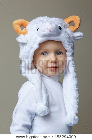 Cute adorable pretty Caucasian baby toddler with large blue eyes wearing a sheep hat hood with yellow horns on top and white shirt standing on a light background looking into the camera New Year concept studio
