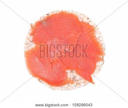 Smoked wild pacific sockeye salmon on organic brown rice cake isolated on white background